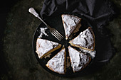 Sliced homemade pie with custard and sugar powder on black plate