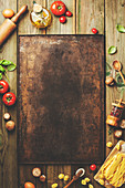 Cooking background: empty rustic baking sheet and italian ingredients