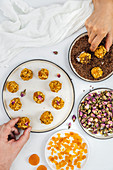 A man and a woman making pumpkin balls with diced apricot, flax seeds and rose petals accompany
