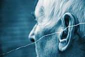 Elderly man using a hearing aid