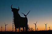 Bull advertising sign and wind turbines at sunset