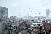 City rooftops through a rain-spattered window