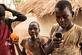 Children eating fruit and using a mobile phone