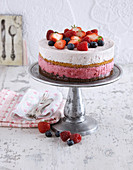 A striped layer cake topped with a trio of fruits