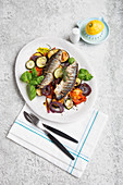 Fried herring on a bed of Mediterranean vegetables