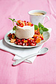 Shaped ricotta cream with a papaya and pomegranate salad
