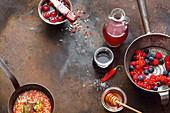 Fresh berries, barbecue marinade in a pan, and cherries in juice and honey