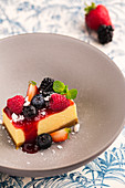 A slice of cheesecake with fruit sauce and fresh berries