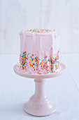 A pink frosted cake with colorful sprinkles on a pink stand