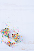 A set of three heart cookie cutters filled with colorful sprinkled on a white surface
