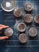 Schokoladen-Traubenkirschen-Muffins mit Puderzucker auf Abkühlgitter
