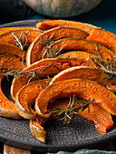 Pumpkin slices baked with rosemary served on gray dish