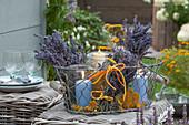 Windlichter und Trockenblumen im Drahtkorb :