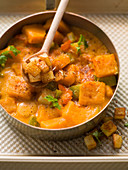Pumpkin cream goulash with potato cubes