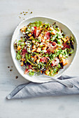 A colourful mixed leaf salad with melons, ham and macadamia nuts
