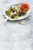 Grilled courgette with olives and tomato salad
