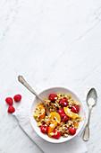 Vegan quinoa muesli with apricots, raspberries and soya yoghurt