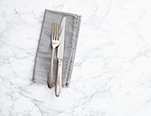 A grey napkin with a knife and fork