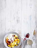 Yellow fruit salad with yoghurt sauce and pomegranate seeds