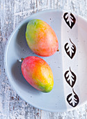 Two whole mangos on a ceramic plate