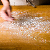 Dusting flour on a butcher block cutting board