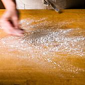 Ein Holzschneidebrett mit Mehl bestauben