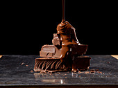 Chocolate sauce being poured on stack of chocolate