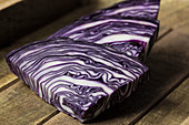 Red cabbage slices on a wooden background
