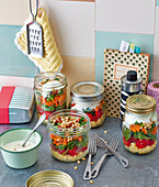 Layered vegetable salad with dates and yoghurt in jars