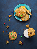 Oatmeal butter cookies with colorful candies with a glass of milk on blue background
