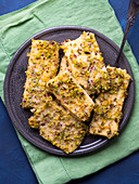 Baked polenta cheese bars topped with pistachio nuts and Parmesan