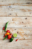 Various chili peppers on a wooden background