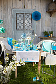 Table set in shades of blue with hand-made decorations in spring garden