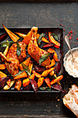 Colourful oven-roasted vegetables with peppered chicken on a baking tray