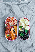 Bento - japanese lunch box: Rice with tomato sauce, fresh cherry toatoes with basil, oven baked sweet potato with black and white sesame seeds, banana, blueberries and lemon balm.