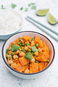Thai vegan curry with sweet potato, green peas, chickpeas, coconut milk and red curry paste
