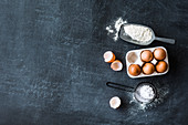 Eggs, flour and icing sugar on a grey surface
