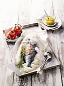 Gilthead seabream in a salt crust with stuffed, grilled tomatoes and aioli