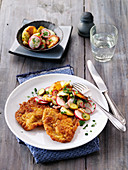 Breaded pork escalope with a fried potato and radish salad