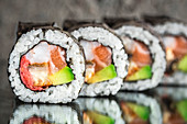 Sushi roll with salmon, shrimps and avocado over concrete background