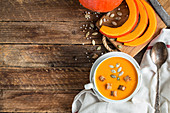 Pumpkin soup puree with seeds and wooden background