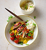 An Asian Style lacquered chicken fillet with vegetables and rice
