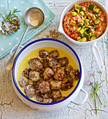 Meatballs in a creamy sauce with tomato and courgette rice