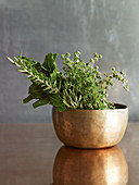 Various fresh herb sprigs in a copper cup