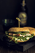 A bagel sandwich with smoked turkey breast, rocket and cucumbers