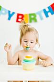 Kleines Mädchen sitzt im Hochstuhl und isst Muffin zum ersten Geburtstag