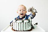 Kleiner Junge sitzt im Hochstuhl und isst Geburtstagstorte