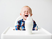 A little boy crying in a highchair in front of a milk bottle