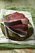 Three slices of raw tuna on a chopping board