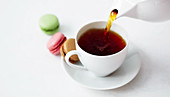 Pouring a cup of tea next to three macarons